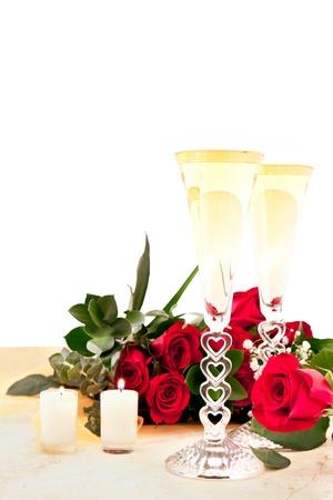 rosas rojas y champagne en una encimera de pizarra con dos velas encendidas para San Valentín