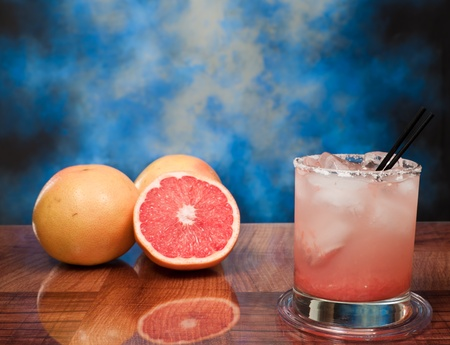 fresh grapefruits on a bar one of them sliced and a tall glass filled with juice and vodka with a salt rim