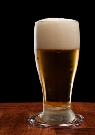 light beer on a wooden bar isolated on a black background