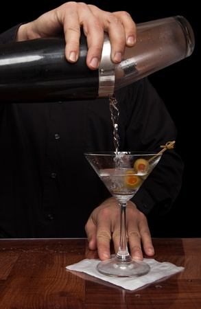 hands of a bartender holding a shaker pouring a drink into a martini glass photo