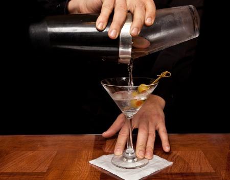 copa martini: manos de un camarero, sosteniendo la coctelera verter una bebida en un vaso de martini