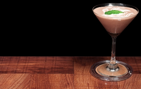chocolate martini garnished with fresh cream and mint sprig on a bar top isolated on black