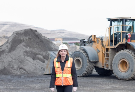 female construction worker with a front loader machine