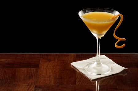 orange martini garnished with a twist isolated on black