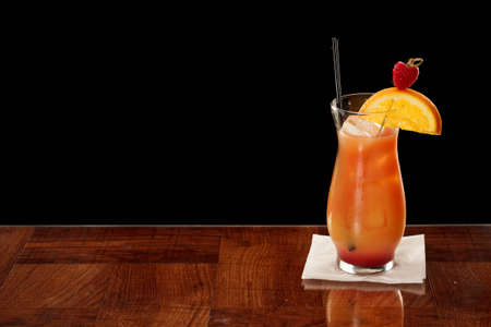 alcohol screwdriver: fresh raspberries and orange juice in a hurricane glass isolated on a black background