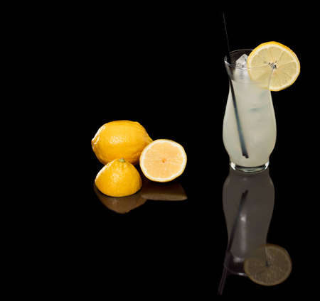 fresh lemonade on a black background with sliced lemons on the side Stock Photo - 12499108