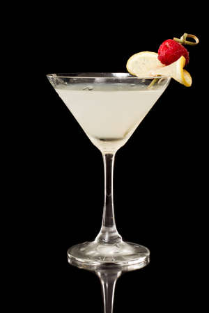 Tropical martini isolated on a black background garnished with a thin slice of lemon and a red raspberry Stock Photo - 12499143