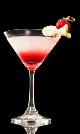 Tropical martini isolated on a black background garnished with a thin slice of lemon and a red raspberry Stock Photo - 12499148