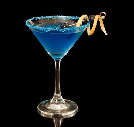 Blue martini garnished with blue sugar rim and lemon twist and berries on a black background
