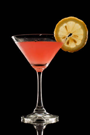 red drink on a black background garnished with a lemon wheel Stock Photo - 12499150