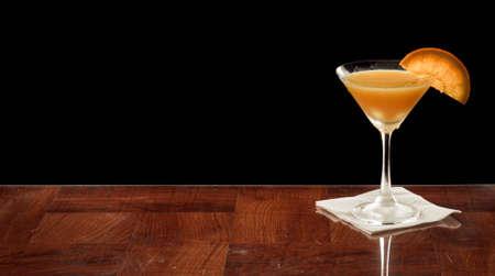 orange martini on a bar top garnished with an orange slice over black photo
