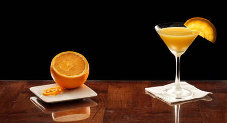 orange martini on a bar top garnished with an orange slice and fresh orange on the side