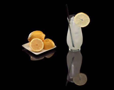 fresh lemonade on a black reflective background, with fresh lemons on a plate Stock Photo - 12499274