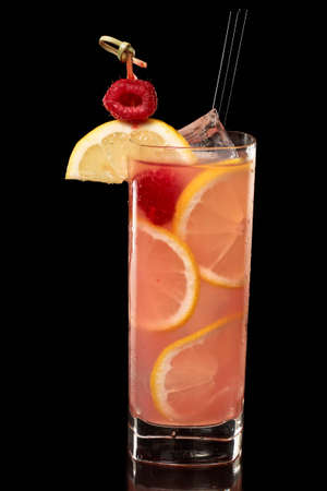 pink raspberry lemonade isolated on a black background garnished with lemon and red reaspberry, tall glass Stock Photo - 12499337