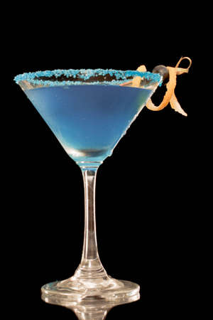 Blue martini garnished with blue sugar rim and lemon twist and berries on a black background Stock Photo - 12499277