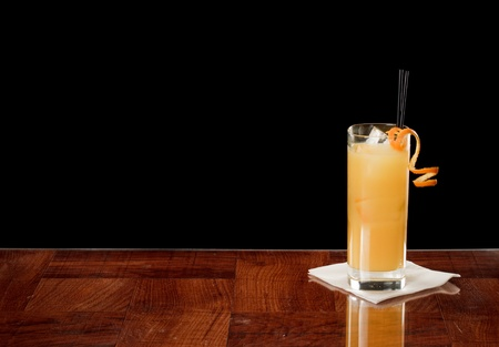 alcohol screwdriver: fresh orange juice and vodka in a collins glass garnished with a orange twist on a bar top Stock Photo