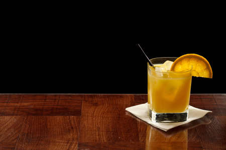 alcohol screwdriver: fresh orange juice in a short glass mixed with vodka and ice isolated on black on a bar top