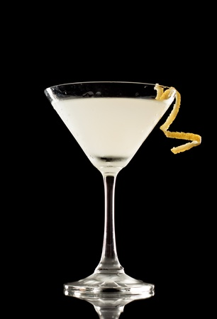 Martini over a black background garnished with a lemon twist Stock Photo - 12499339