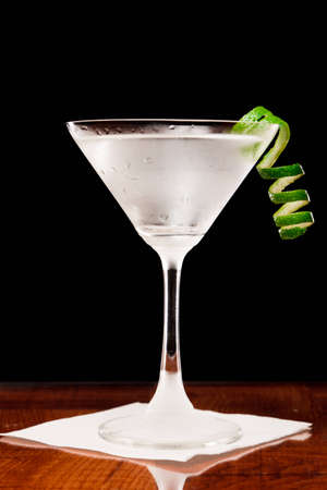 martini on a bar top garnished with a fresh lime twist Stock Photo - 12499659