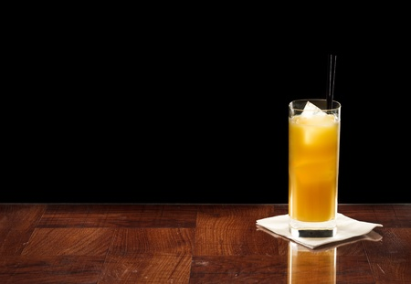screwdriver cocktail on a bar top isolated on a black background