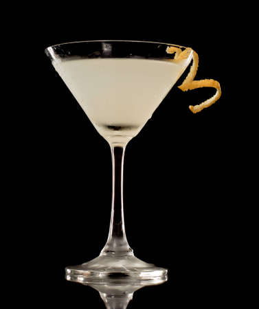 twist: Martini over a black background garnished with a lemon twist