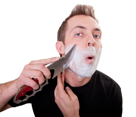 Man shaving with a very large knife isolated on a white background