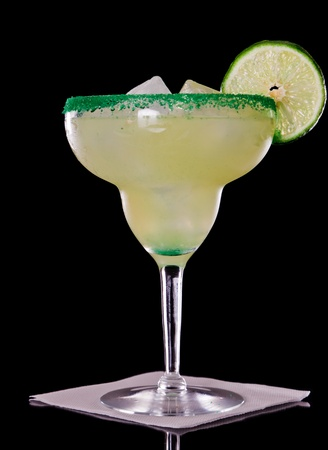 Margarita isolated on a black background garnished with a green sugar rim