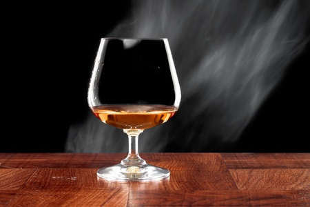 Brandy snifter on a bar top isolated on a black background Stock Photo - 12752075