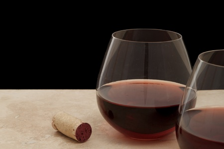 two stemless glasses of red wine served on a bar top isolated on black photo