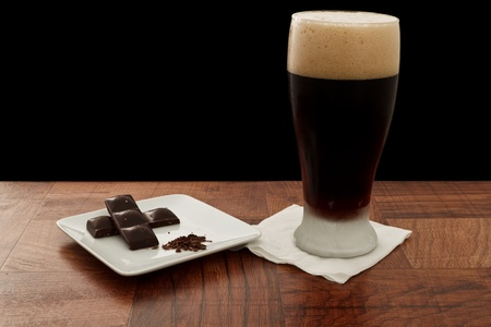 alcohol drink served in a chilled glass on a bar top isolated on black paired with chocolate Stock Photo