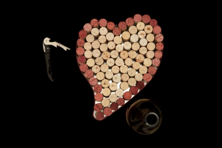 Stack of wine corks as a flat textured heart shaped background with corkscrew and bottle photo