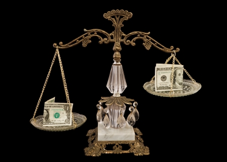 weighing scale: scale balancing a one dollar bill and a one hundred bill isolated on a black background
