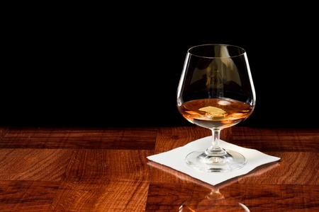 Brandy snifter on a bar top isolated on a black background Stock Photo