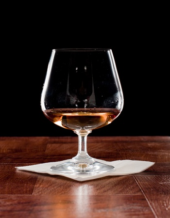 Brandy snifter on a bar top isolated on a black background photo