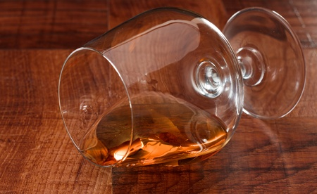 Brandy snifter onits side filled to the rim on a bar top Stock Photo - 12911076