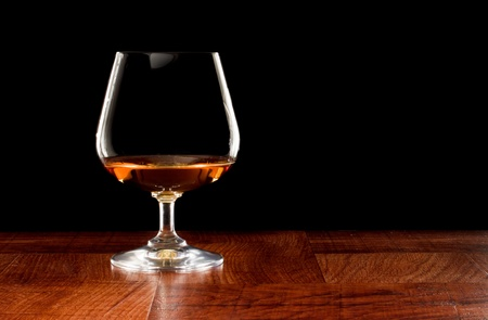 Brandy snifter on a bar top isolated on a black background Stock Photo - 12911027