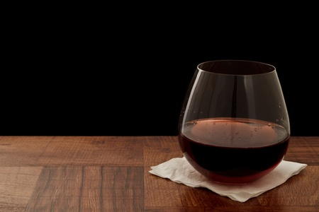 steamless glass of red wine on a bar top isolated on a black background