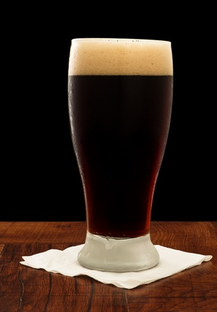 irish stout served in a chilled glass on a bar top isolated on black