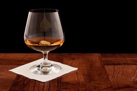 glass of whiskey served on a bar top isolated on a black background