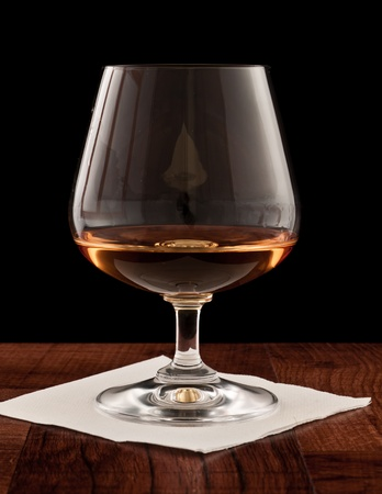 glass of whiskey served on a bar top isolated on a black background photo