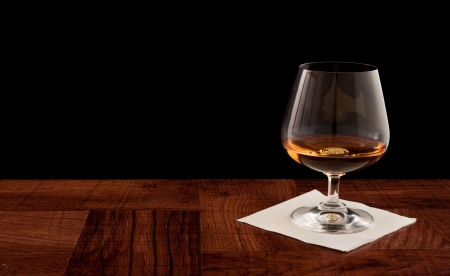 glass of whiskey served on a bar top isolated on a black background Stock Photo - 12911024
