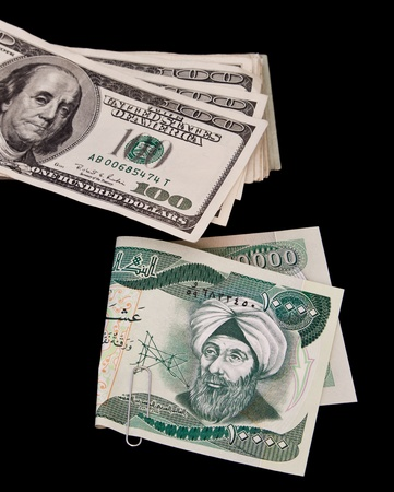 ten thousand Iraqui dinar bill and a bunch of hundred dollar bills isolated on a black background Stock Photo - 12911068