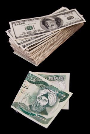 basra: ten thousand Iraqui dinar bill and a bunch of hundred dollar bills isolated on a black background Stock Photo