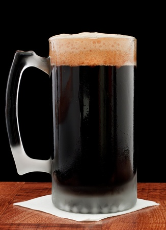 dark beer isolated on a black backgoud served in a chilled mug Stock Photo - 13030750