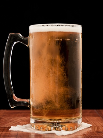 light pilsner served in a frosted mug isolated on a black backgound Stock Photo - 13030758