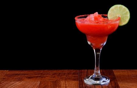 slushy: strawberry margarita isolated on a black background served on a bar top