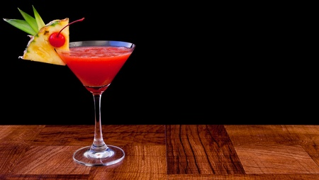 tropical cocktail isolated on a black background served on a bar top photo