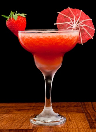 fresh pureed strawberry margarita isolated on a black background