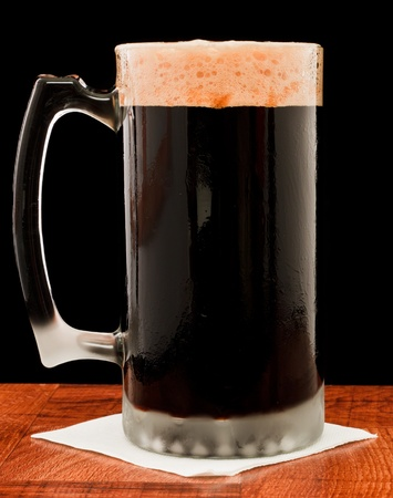 dark beer isolated on a black backgoud served in a chilled mug