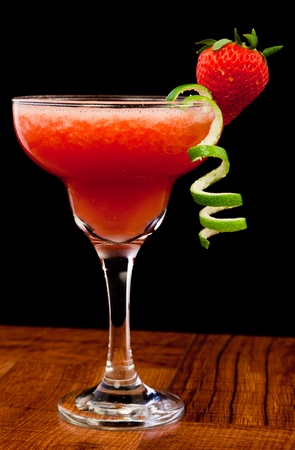 fresh pureed strawberry margarita isolated on a black background photo